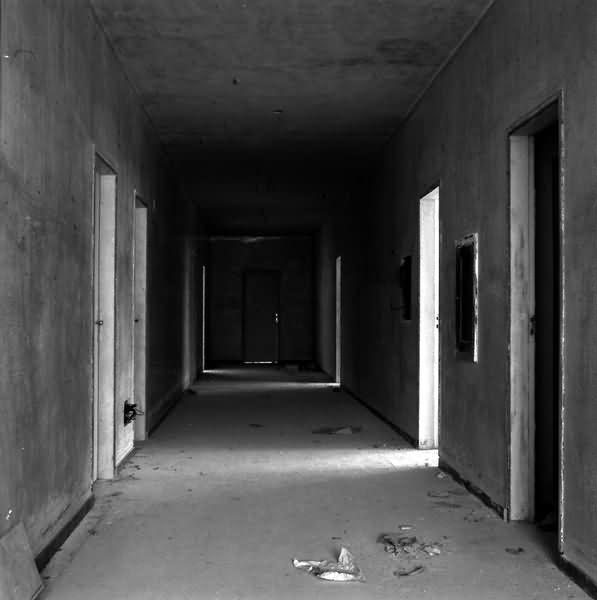 Fotografia de um corredor formado por seis portas nas laterais e uma na parede de centro. As frestas na parede dinamizam claridade e escurecimento ao longo do corredor, conferindo profundidade e volume. A refração da luz produz novas formas geométricas nesse paralelepípedo. Volumes e contornos adquirem formas, enquanto o espaço se expressa através da oscilação da luminosidade e os tons de cinza dinamizados pela reflexão da luz.
