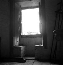 """Foto preto e branca. Uma janela de abrir tipo bandeira, de madeira, está aberta. Está de dia. A claridade entra para uma saleta de paredes robertas de reboco, brancas. No peitoril da janela, há dois bancos de alvenaria interligados à parede. Estes bancos dão à janela o nome de """"Janela Conversadeira"""". O piso é de pedra lisa. No canto direito, há três cetros grandes encostados na parede. Em frente aos cetros, aparece metade de uma cuba, aparentemente instalada na parede."""