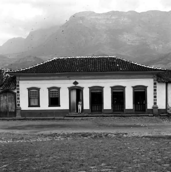 Uma casa colonial em Catas Altas, Minas Gerais é mostrada de frente, com suas quatro portas e duas janelas. Um homem está de pé encostado em uma das portas. Por trás da casa avista-se a serra, parcialmente oculta pela neblina. A foto foi tirada em 1960 pelo fotógrafo Mazonnni.