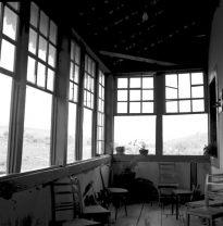 Imagem em preto e branco da varanda de uma fazenda, coberta em forma de L, com sete janelas retas, abertas, com vidros quadriculados. Tem sete cadeiras espalhadas pela varanda, vasinhos de plantas em uma das janelas e em alguns cantos do ambiente.
