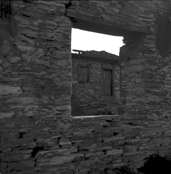 Vista da janela de uma residencia feita em pedra, que mostra uma outra residencia antiga ao fundo construída também com pedras sobrepostas com janelas e portas de madeira.