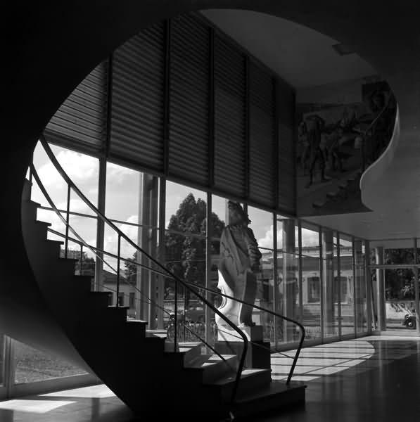 Foto antiga em preto e branco, com escadaria e hall da Escola de Arquitetura da UFMG em primeiro plano. Contém escultura barroca (réplica em gesso de um profeta do Aleijadinho), bem como casas e carros antigos ao fundo, vistos pelos panos de vidro do hall.