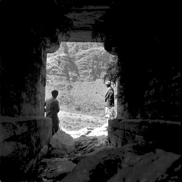 Foto antiga em preto e branco tirada dentro de um túnel com as bordas mostrando as paredes e o chão de pedra. Ao fundo duas pessoas observando uma paisagem rochosa.