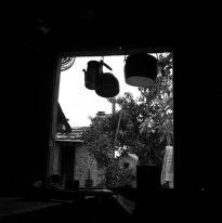 Imagem em preto e branco de uma janela. Há uma chaleira e duas panelas penduradas na parte superior da janela. Ao fundo há uma outra casa de tijolos que está com a porta aberta, do lado direito da imagem tem a folhagem de uma árvore e um varal em que possui uma toalha pendurada.