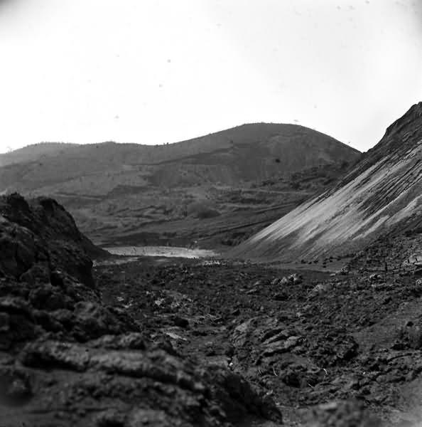 Paisagem natural montanhosa, com elevações suaves. A foto foi feita aos pés de uma montanha, mirando uma outra elevação aos fundos. O leito pedregoso e a ausência de vegetação sugerem tratar-se de área minerada. No terço superior da foto abre-se um céu claro.